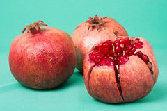 Pomegranate isolated on white background. Two pomegranates placed on green background. Studio photo stock photo