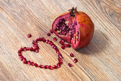 Pomegranate and its heart shaped seeds. Pomegranate and its seeds laid out in the shape of heart on a wooden texture Royalty Free Stock Images