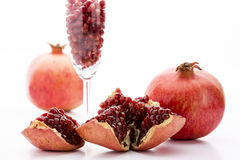 Pomegranate and its seeds. Ripe, deep red pomegranate seeds, embedded in its reddish fruit skin. Separated seeds in a slim glass. Two whole pomegranate fruits Stock Image
