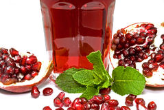 Pomegranate juice. Tumbler with pomegranate juice decorated with pomegranate halves, seeds and mint leaves Stock Photography