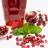 Pomegranate juice. Tumbler with pomegranate juice decorated with pomegranate halves, seeds and mint leaves Royalty Free Stock Photography