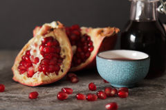 Pomegranate juice in a blue circle and juicy red garnet. On a gray stone background stock photography