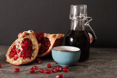 Pomegranate juice in a blue circle and juicy red garnet. On a gray stone background stock image