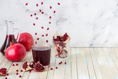 Pomegranate juice and fruit slices. Grains are flying over the g Stock Photo