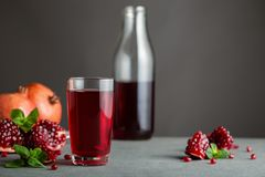 Pomegranate juice in a glass on gray background. royalty free stock photos
