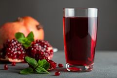 Pomegranate juice in a glass on gray background. stock photos