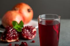 Pomegranate juice in a glass on gray background. royalty free stock images