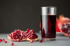 Pomegranate juice in a glass on gray background stock photography