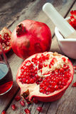 Pomegranate, juice in glass, mortar and pestle on wooden table Royalty Free Stock Photos