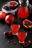 Pomegranate juice in glass and pitcher on the black background Stock Images