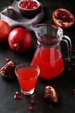Pomegranate juice in glass and pitcher on a black background Stock Images