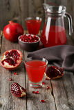 Pomegranate juice in glass and pitcher on the grey wooden background Stock Images
