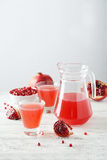 Pomegranate juice in glass and pitcher on the white wooden background Royalty Free Stock Photography