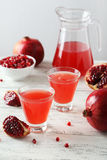 Pomegranate juice in glass and pitcher on the white wooden background Stock Image
