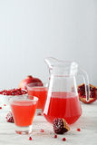 Pomegranate juice in glass and pitcher on a white wooden background Royalty Free Stock Photo