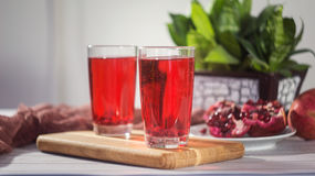Pomegranate juice in a glass and ripe pomegranate Royalty Free Stock Photos