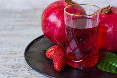 Pomegranate juice in a glass. Surrounded by fruit Stock Photos