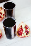 Pomegranate juice in glass surrounded by pomegranate halves. Pomegranate juice in glass surrounded by pomegranate halves stock photo