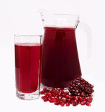 Pomegranate juice in pitcher and pomegranates  on white Royalty Free Stock Photo