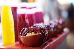 Pomegranate juice and red ruby fruit are cooked on the table. royalty free stock photos