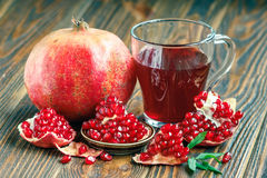 Pomegranate juice with ripe fresh punica granatum fruits. Glass of pomegranate juice with ripe fresh punica granatum fruits with leaves on wooden table close-up Stock Photography