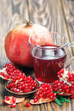 Pomegranate juice with ripe fresh punica granatum fruits. Glass of pomegranate juice with ripe fresh punica granatum fruits with leaves on wooden table close-up Stock Photos