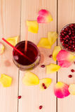 Pomegranate and juice. Rose petals. Royalty Free Stock Photos
