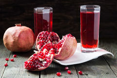 Pomegranate juice and slices of pomegranate with grains Royalty Free Stock Photo