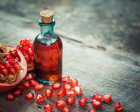 Pomegranate juice or tincture and garnet fruit with seeds. On kitchen table. Selective focus stock photo