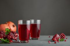 Pomegranate juice in two glasses on gray background. stock photography
