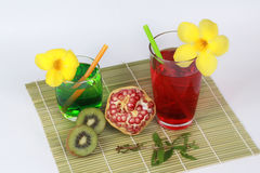 Pomegranate juice and two tone of kiwi juice  with peeled ripe  pomegranate and halves kiwi on bamboo. Pomegranate juice andTwo tone of kiwi juice are popular Royalty Free Stock Photos