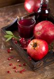 Pomegranate juice on a wooden background Royalty Free Stock Images