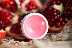 Pomegranate lip gloss on a wooden surface. Closeup stock photo