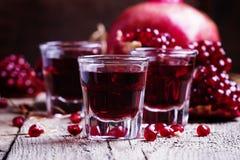 Pomegranate liqueur, old wooden background, selective focus stock images