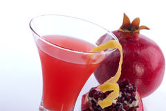 Pomegranate martini. Closeup of Pomegranate martini and broken open pomegranate over white. Vodka, pomegranates juice and lemon twist. Most popular cocktails stock images