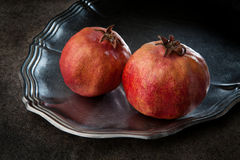 Pomegranate on a metal plate. Two ripe juicy pomegranate on a metal plate Stock Image