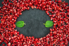 Pomegranate with mint on a black background. Scattered ripe pomegranate grains. macro Stock Image