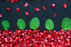 Pomegranate with mint on a black background. Scattered ripe pomegranate grains. macro Stock Photos