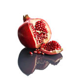 Pomegranate opened up on reflective surface Stock Images