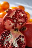 Pomegranate and Oranges in Morning Light. Sliced and halved pomegranate with oranges in the background Stock Photography