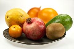 Pomegranate, papaya, mango - a set of exotic fruits on metal plates. Studio, isolated stock photography