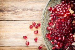Pomegranate. Pomegranate particles on a green plate and wooden table stock photo