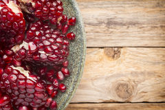 Pomegranate. Pomegranate particles on a green plate and wooden table royalty free stock photography