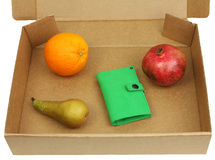 Pomegranate, pear, orange and green wallet in a box Royalty Free Stock Photography