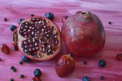 Pomegranate on the pink wooden board. Tropical fruits on purple wooden board, with seeds and berries royalty free stock photography