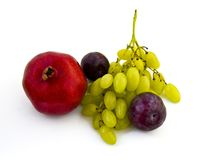 Pomegranate, plums and grapes on white background Stock Images