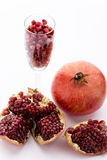 Pomegranate, Punica granatum. One whole pomegranate, Punica granatum. Next to it are pieces of a broken-up pomegranate. A champagne glass filled with ripe Stock Images