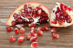 Pomegranate. Red pomegranate broken on a wooden board Stock Photography