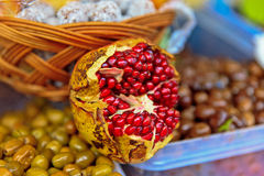 Pomegranate. Red juicy pomegranate on olives Royalty Free Stock Photo