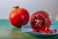Pomegranate and red seeds of fruit on a blue plate. Beautiful bright tropical fruit on a green table. stock photos